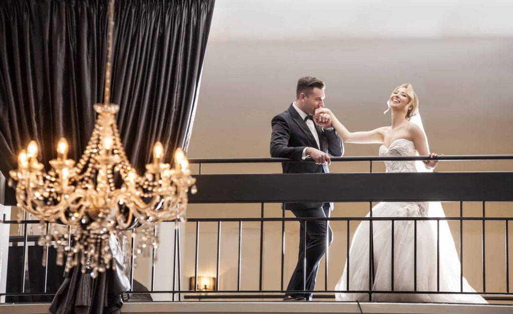 man kissing brides hand on vogue balcony